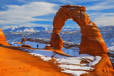 Hiker at Delicate Arch in winter, Arches National Park, Utah