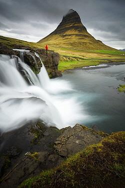 Hiker at waterfall, Kirkjufellsfoss, Snaefellsnes Peninsula, Iceland