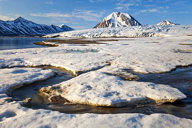 Creek flowing through ice with glacier and mountain in background, Comfortlessbreen, Engelsbukta, Spitsbergen, Svalbard, Norway