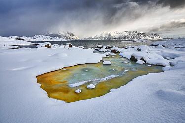 Geothermal water flowing into ocean in winter, Austvagoya, Norway