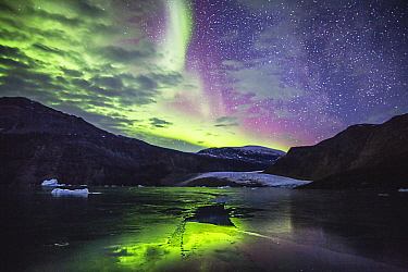 Aurora borealis over glacier and coastal mountains, Scoresby Sound, Greenland
