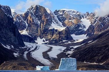 Icebergs along coastal mountains and glacier, Scoresby Sound, Greenland