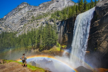 Hiker near waterfall and rainbow, Nevada Fall, Yosemite National Park, California