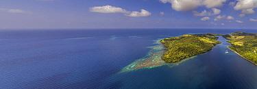Ship near tropical island, Normanby Island, Papua New Guinea