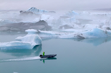 Boater, in an inflatable boat, speeding by icebergs from Vatnajokull Glacier, Jokalsarlon Lagoon, Iceland  -  Cyril Ruoso