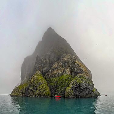 Boat near basalt cliffs of island, Franz Josef Land, Russia