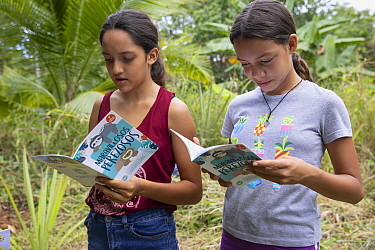 Local students reading sloth conservation booklet during community education session, Sloth Conservation Foundation, Puerto Viejo de Talamanca, Costa Rica