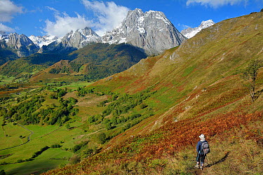 Hiker overlooking the Lescun circus in autumn, Pic d'Anie, Billare and Dec de Lhurs withe clouds, Pyrenees, France