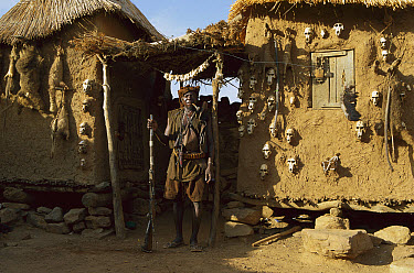Dogon hunter in front of his hut showing various primate skulls, Sahel Desert, Mali, west Africa  -  Ingo Arndt