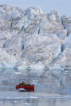 Tourist boat in front of large iceberg at midnight, end of June, mid-summer night, Greenland  -  Theo Allofs