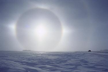 Sundogs, also known as mock sun, with car on the horizon above a snow field, Minnesota  -  Jim Brandenburg