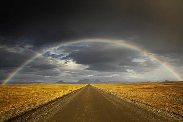 Rainbow over dirt road, Iceland  -  Chris Stenger/ Buiten-beeld