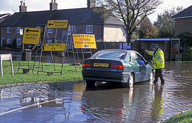 Policeman directing diverted traffic through flooded village road, West Sussex, England  -  Angela Hampton/ FLPA