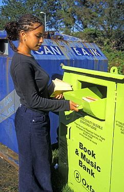 Recycling, mixed race teenage girl, putting unwanted books into recycling book bank, England  -  Angela Hampton/ FLPA