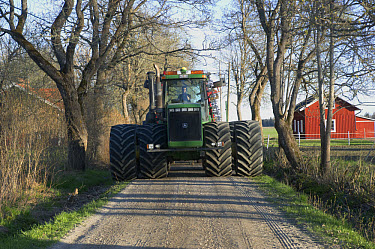 John Deere tractor, with dual wheels, driving along small road on way to fields, Uppland, Sweden, may  -  Bjorn Ullhagen/ FLPA