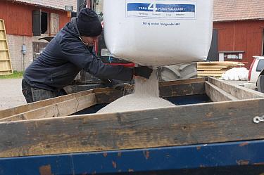 Farmer emptying bag of nitrogen granular fertilizer granules into fertilizer spreader, Sweden, may  -  Bjorn Ullhagen/ FLPA