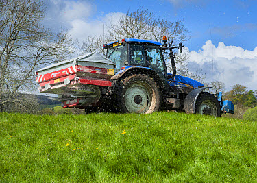 Tractor with spreader, spreading granular fertilizer on grassland, Castle Bolton, Redmire, North Yorkshire, England, may  -  John Eveson/ FLPA