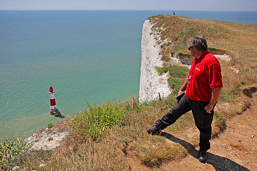 Chaplain on patrol in attempt to find and stop any potential 'jumpers' at infamous clifftop suicide spot, standing at edge of chalk cliff overlooking lighthouse, Beachy Head Lighthouse, Beachy Head, E...  -  John Watkins/ FLPA