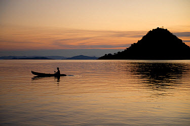 Person rowing kayak from island at sunset, Kelor Island, near Flores Island, Komodo National Park, Lesser Sunda Islands, Indonesia, July  -  Colin Marshall/ FLPA