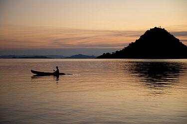 Person rowing kayak from island at sunset, Kelor Island, near Flores Island, Komodo National Park, Lesser Sunda Islands, Indonesia, July  -  Colin Marshall/ FLPA