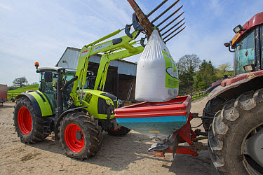 Claas tractor with front loader forks, loading big bags of fertiliser into fertiliser spreader on farm, near Longridge, Lancashire, England, April  -  John Eveson/ FLPA