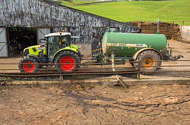 Claas tractor with slurry tanker, loading slurry from lagoon, near Longridge, Lancashire, England, April  -  John Eveson/ FLPA