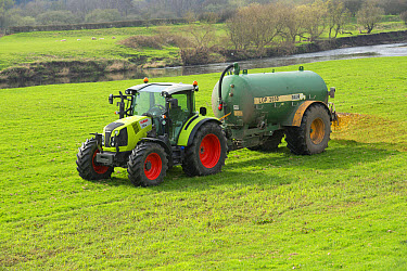 Claas tractor with slurry tanker, spreading slurry on grassland near river, near Longridge, Lancashire, England, April  -  John Eveson/ FLPA