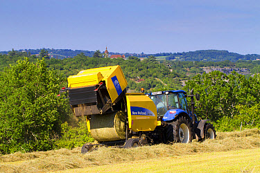 Contractor with New Holland T5.95 tractor and New Holland BR7060 round baler, baling hay in field, near Rocamadour, Lot Region, France, May  -  Richard Becker / FLPA