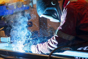 Factory worker welding in a manufacturing plant.