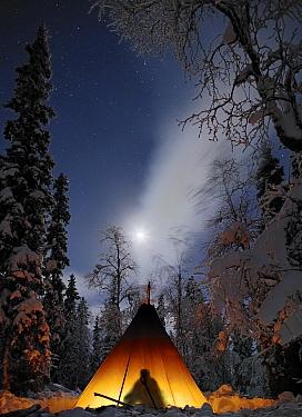 Man silhouetted inside Tepee with light, full moon, Lapland, Finland, January 2006  -  Jorma Luhta/ npl