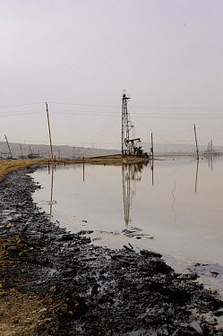 Oil Well and beam pump with pollution in subsidence lagoon, Baku, Azerbaijan, February 2008  -  Graham Eaton/ npl