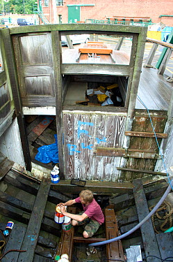 Man preparing paint in the hull of traditional Danish Fishing boat, Bristol Floating Harbour, UK July 2008, Model Released  -  Rob Cousins/ npl