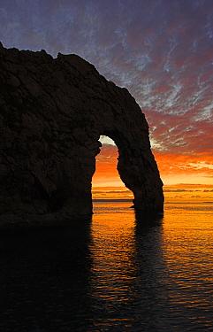 Sun setting through the arch at Durdle Door, Jurassic Coast World Heritage Site, Dorset November  -  Peter Lewis/ npl