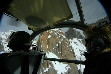 Rear view of pilot and director Vanessa Berlowitz filming in the Karakoram Mountains, Himalayas, Pakistan From Pakistani military helicopter for BBC series Planet Earth, April 2005  -  Jeff Wilson/ npl