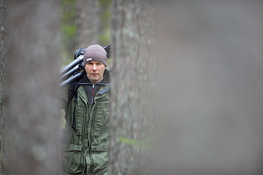 Photographer, Erlend Haarberg, carrying tripod in forest, Bergslagen, Sweden, April 2009  -  WWE/ E. Haarberg/ npl