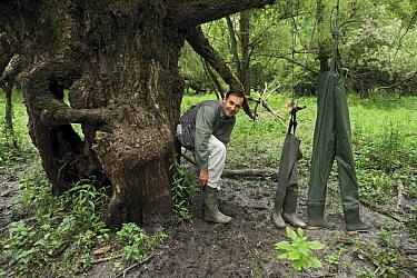Photographer, Elio della Ferrera, with selection of waterproof boots, wellingtons and trousers Lonjsko Polje Nature Park, Croatia Bosnia and Herzegovina border, June 2009  -  WWE/ della Ferrera/ npl