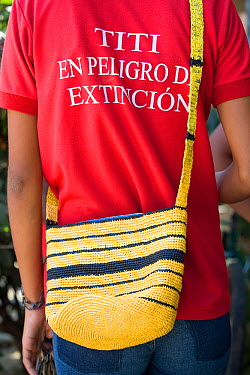 Colombian woman wears a tamarins in danger of extinction t-shirt and an eco-mochila (bag) woven from recycled plastic bags Los Limites, Colombia, South America February 2008  -  Lisa Hoffner/ npl