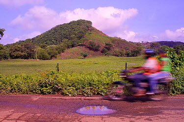 Motorcycle whizzes past pasture and half-denuded hill (once Cotton-top tamarin habitat) Colombia, South America  -  Lisa Hoffner/ npl