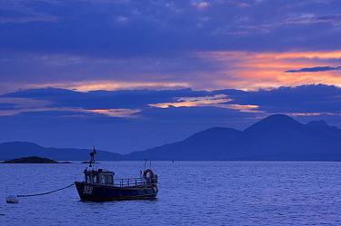 Fishing boat moored at dusk at Badicaul, nr the Kyle of Lochalsh, with the Isle of Skye beyond, Wester Ross, Scotland  -  David Noton/ npl