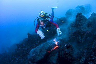 Diver Bud Turpin observes erupting pillow lava at ocean entry of Kilauea Volcano on Hawaii Island, Hawaii Heat waves rising from the lava distort his image Model released MR 381  -  Doug Perrine/ npl