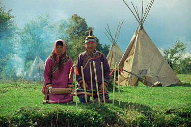 Udege couple in traditional clothing sitting outside traditional tent, Sikhote Alin, Primorsky region, Russia (Ussuriland)  -  Yuri Shibnev/ npl
