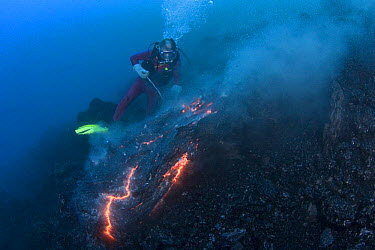 Diver Bud Turpin observes erupting pillow lava at ocean entry of Kilauea Volcano on Hawaii Island, Hawaii, Heat waves rising from the lava distort his image Model released MR 381  -  Doug Perrine/ npl