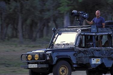Simon King presenter of Big Cat Diary in vehicle with film camera Masai Mara NR Kenya 2000  -  Angela Scott/ npl