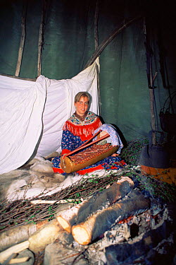 Sami woman in lavvu (tent) with traditional wooden baby cradle, Karaskok, Samiland (Lapland), Finnmark, Northern Norway 1997  -  Pete Oxford/ npl