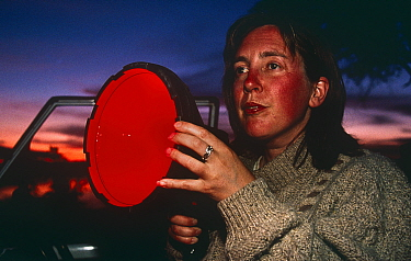 Amanda Barrett, producer, holding infra-red light for night filming of Leopards, South Luangwa NP Zambia, 1996  -  Owen Newman/ npl