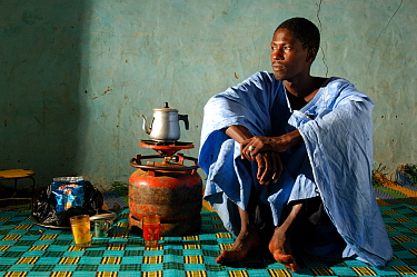Fulani man brewing tea on calor gas in his house wearing traditional Mauritanian costume, South Mauritania, West Africa, 2005  -  Laurent Geslin/ npl