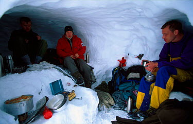 Melting snow for cooking inside a snow hole shelter Finse, Hardangervidda, Norway  -  Asgeir Helgestad/ npl
