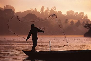 River fisherman throwing net from boat Borneo, Malaysia  -  Jurgen Freund/ npl