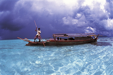 Bajau fisherman in traditional Lepa boat with rain clouds behind, Pulau Gaya, Borneo, Malaysia  -  Jurgen Freund/ npl