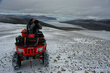 Cameraman, Mark Smith, on an all-terrain-vehicle searching for Arctic wolves, Ellesmere Island, Nunavut, Canada, June 2008 Taken on location for the BBC series, Frozen Planet  -  Jeff Wilson/ npl
